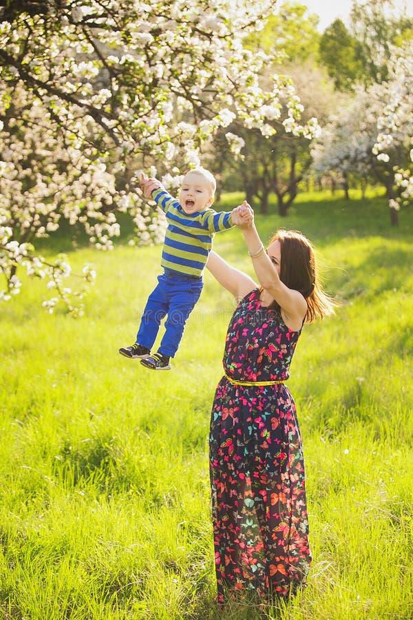 Weinig baby op handen van moeder vrouw het spelen met buiten kind stock foto