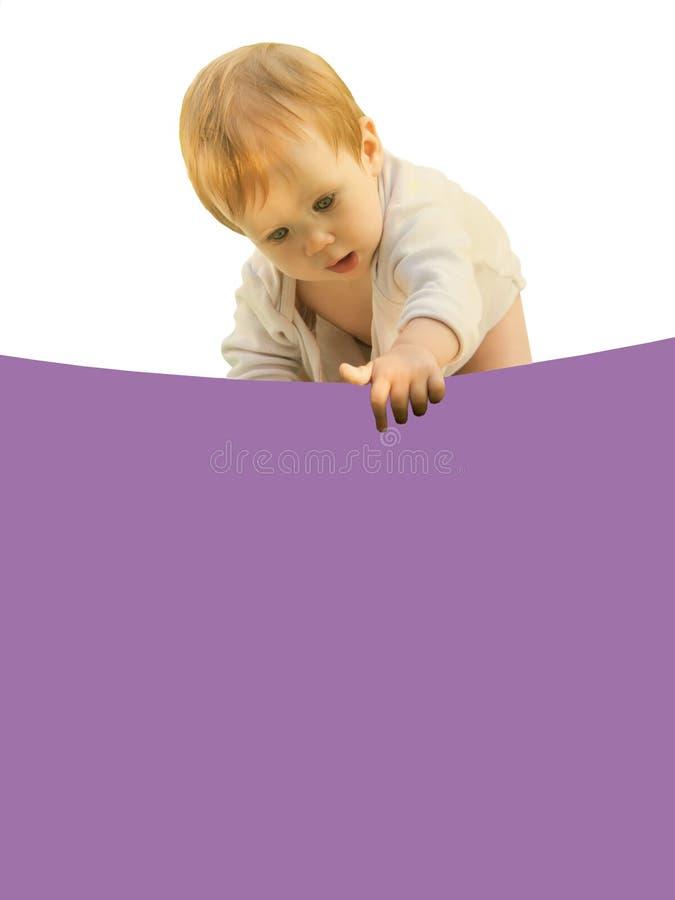 Weinig baby van het babymeisje boog merkwaardig over het gekleurde blad royalty-vrije stock foto's
