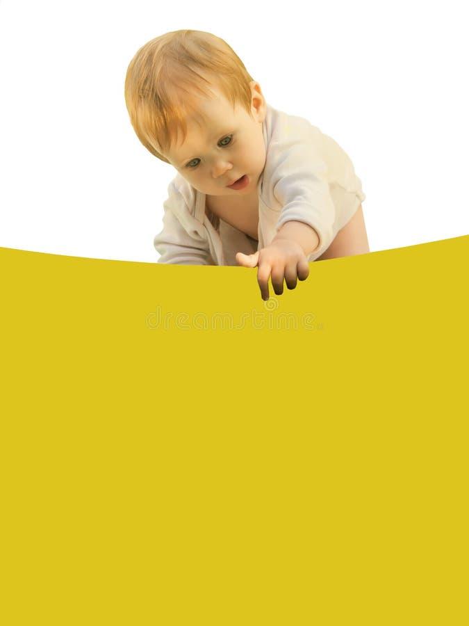 Weinig baby van het babymeisje boog merkwaardig over het gekleurde blad stock fotografie