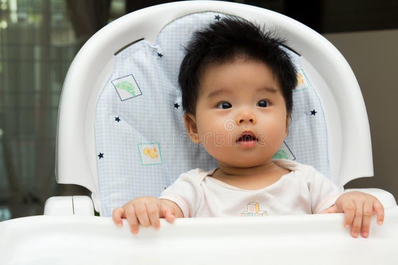 Weinig baby zit op een hoge stoel stock fotografie