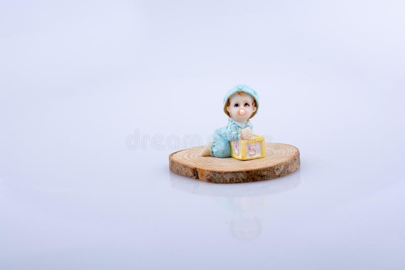 Weinig babycijfer aangaande een stuk van hout royalty-vrije stock foto
