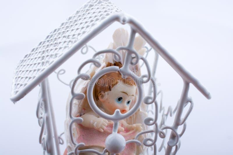 Weinig babycijfer in een kooi stock foto's