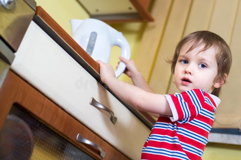 Weinig babyjongen bereikt eletrical ketel met heet water stock foto's