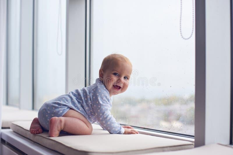 Weinig babyjongen crawlibg dichtbij groot venster royalty-vrije stock foto