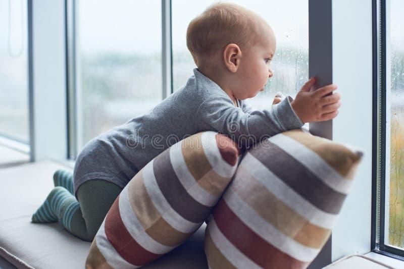 Weinig babyjongen crawlibg dichtbij groot venster op de hoofdkussens stock afbeeldingen