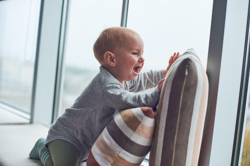 Weinig babyjongen crawlibg dichtbij groot venster op de hoofdkussens royalty-vrije stock afbeelding