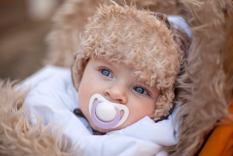 Weinig babyjongen in de warme winter kleedt openlucht stock fotografie