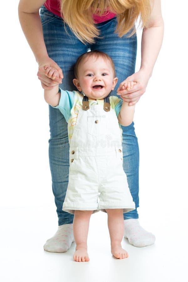 Weinig babyjongen die eerste stappen met moedersteun doen royalty-vrije stock afbeeldingen