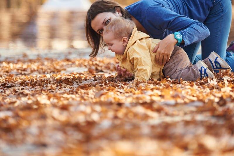 Weinig babyjongen die met moeder onder de gevallen bladeren in het de herfstpark kruipen bij zonnige dag royalty-vrije stock foto's