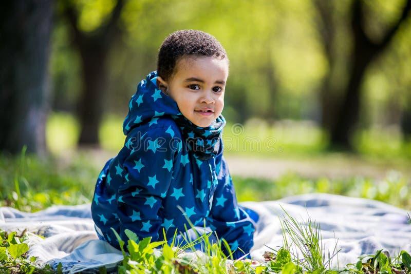 Weinig babyjongen die op de speelplaats in het de lentepark spelen royalty-vrije stock afbeelding