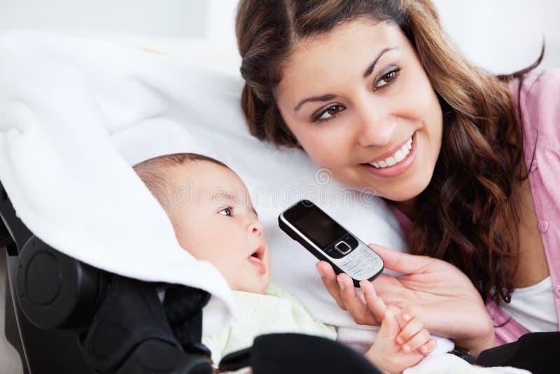 Weinig babyjongen die op de telefoon probeert te spreken royalty-vrije stock foto