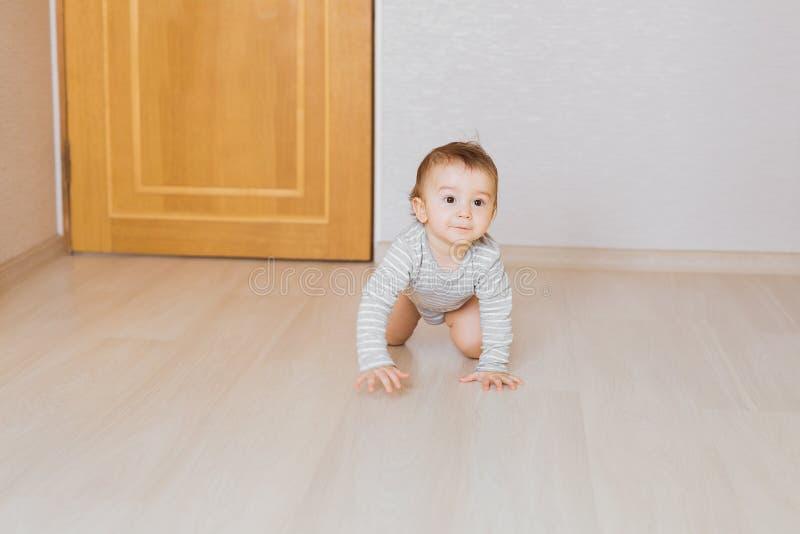 Weinig babyjongen die op de vloer thuis kruipen royalty-vrije stock fotografie