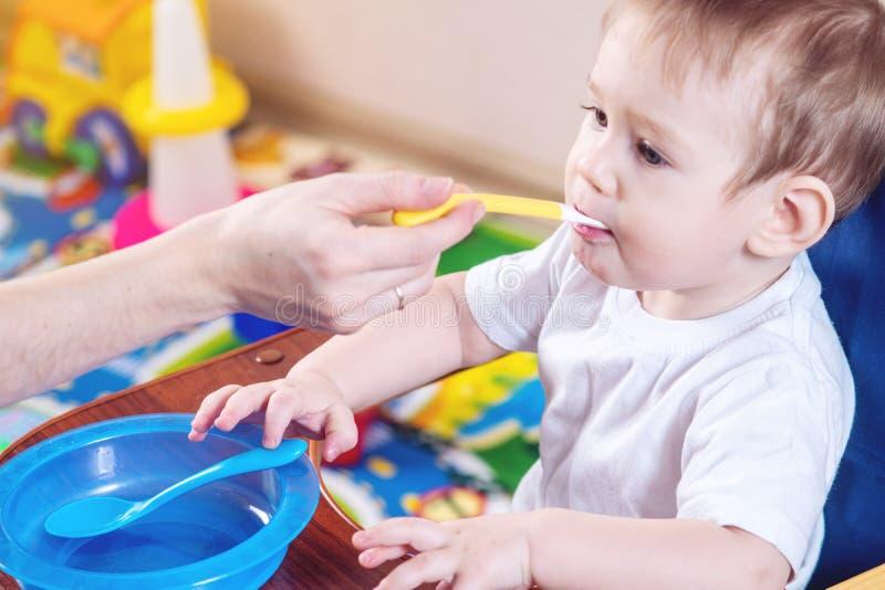 Weinig babyjongen die op een stoel in de keuken eten Mammavoer die ter beschikking een lepel van havermoutpap houden royalty-vrije stock fotografie