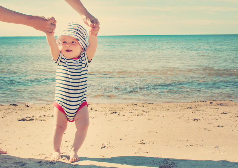 Weinig babyjongen die op het strand in de zomerdag lopen stock afbeeldingen