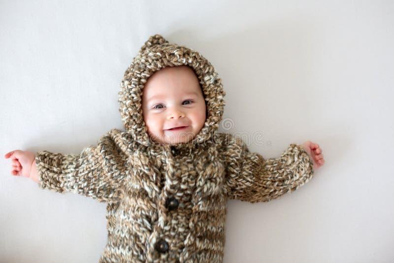 Weinig babyjongen die thuis met zacht teddybeerspeelgoed spelen, het liggen royalty-vrije stock afbeeldingen