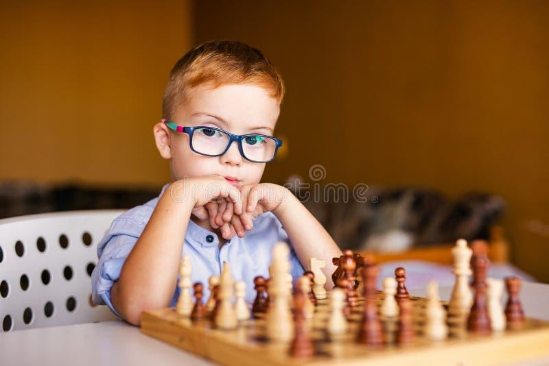 Weinig babyjongen met benedensyndroom die met grote blauwe glazen schaak in kleuterschool spelen stock afbeeldingen