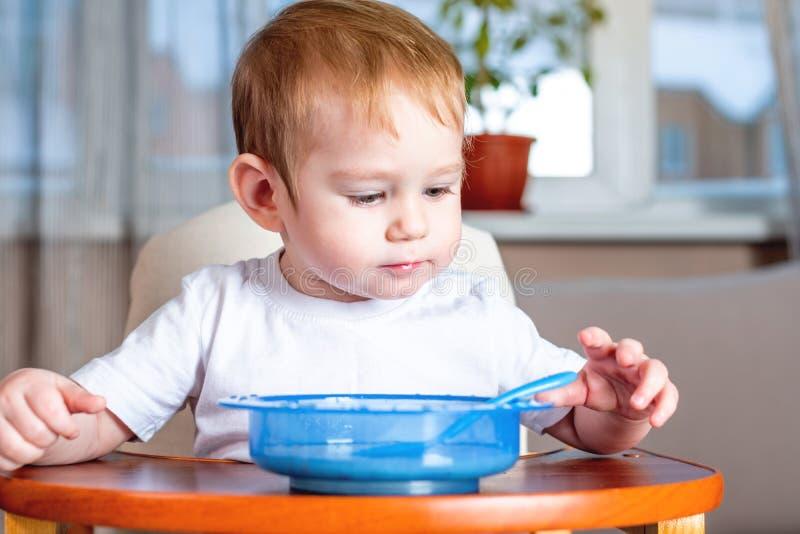 Weinig babyjongen met een lepel leren te eten zelf die in de keuken Concept gezond babyvoedsel royalty-vrije stock fotografie