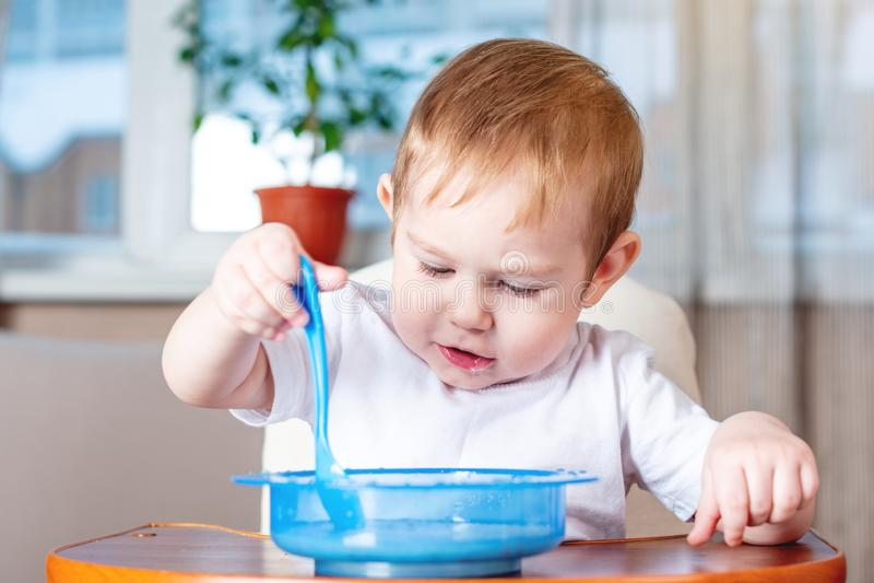 Weinig babyjongen met een lepel leren te eten zelf die in de keuken Concept gezond babyvoedsel royalty-vrije stock afbeelding
