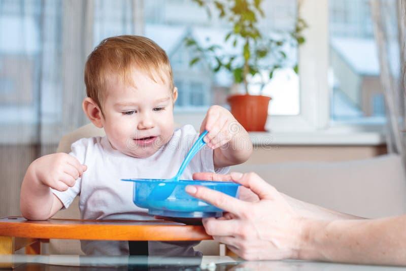 Weinig babyjongen met een lepel zelf die bij de jonge geitjes leren te eten dient in de keuken in Concept gezond babyvoedsel royalty-vrije stock afbeelding