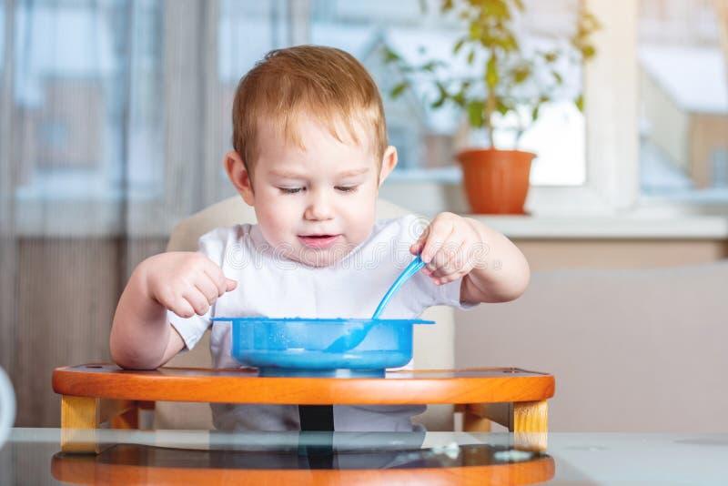 Weinig babyjongen met een lepel zelf die bij de jonge geitjes leren te eten dient in de keuken in Concept gezond babyvoedsel royalty-vrije stock afbeeldingen