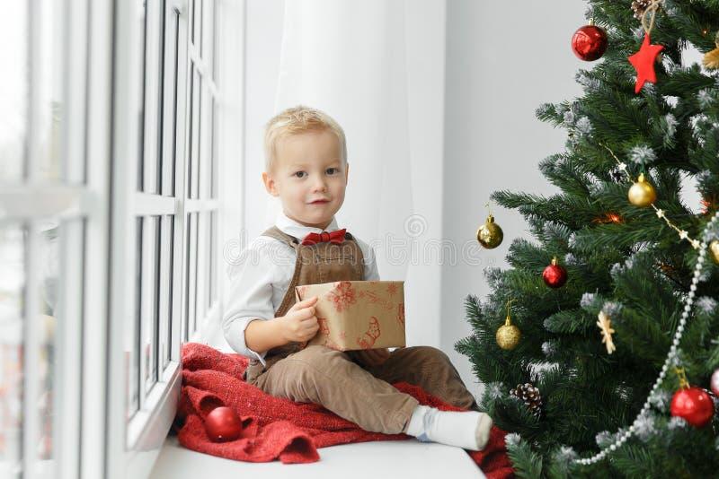 Weinig babyjongen met heden in zijn handen die dichtbij Kerstboom zitten en camera bekijken royalty-vrije stock afbeeldingen