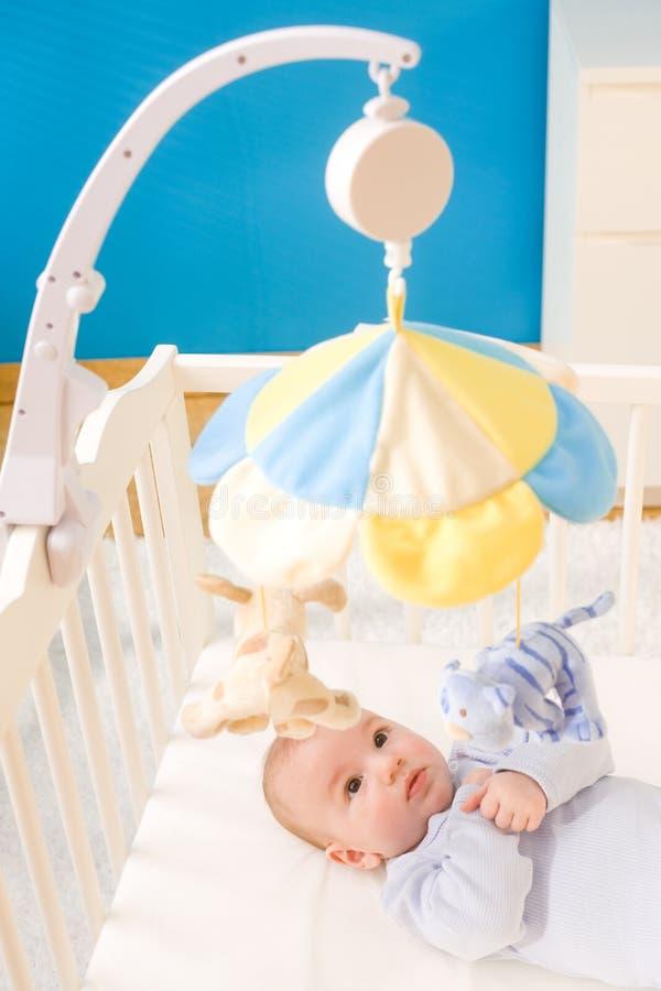 Weinig babyjongen op voederbak stock afbeelding