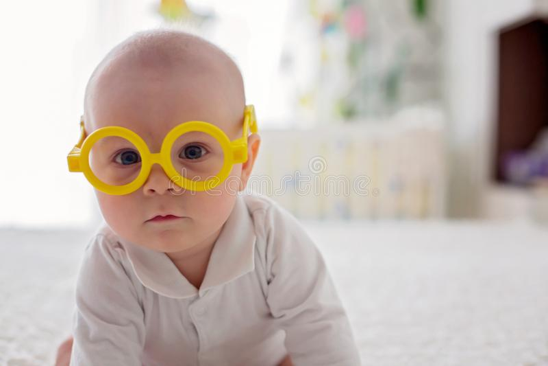 Weinig babyjongen, peuter, die thuis met grappige oogglazen spelen royalty-vrije stock afbeeldingen