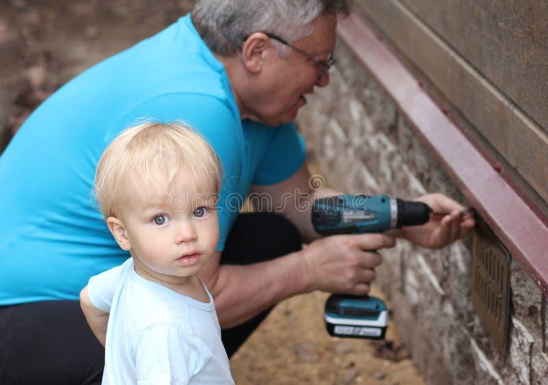 Weinig babykleinzoon en zijn grootvader werken met schroevedraaier royalty-vrije stock afbeeldingen