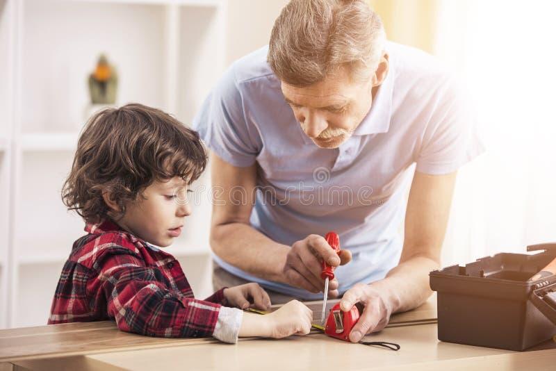Weinig babykleinzoon en zijn grootvader werken met schroevedraaier stock afbeelding