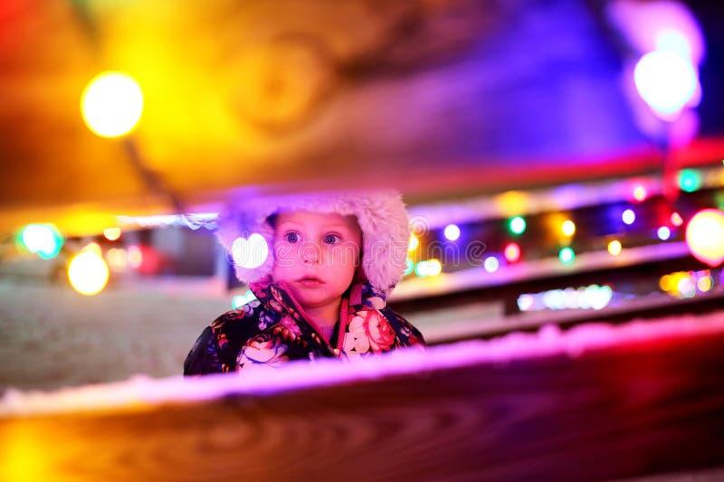 Weinig babymeisje buiten het bekijken Kerstmislichten royalty-vrije stock foto