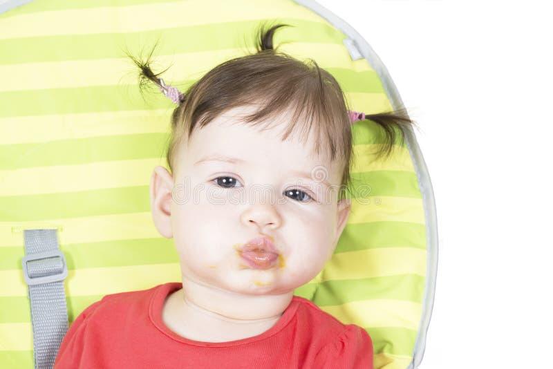 Weinig babymeisje dat een plantaardige puree eet stock fotografie