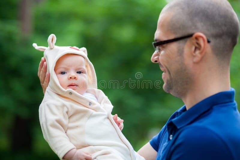 Weinig babymeisje in de wapens van haar vader stock afbeelding