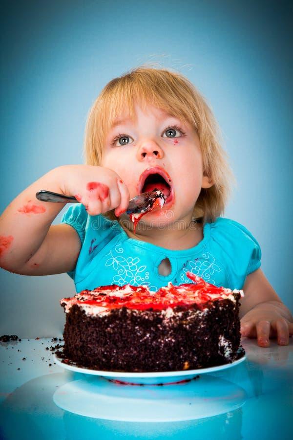 Weinig babymeisje die cake eten stock afbeelding