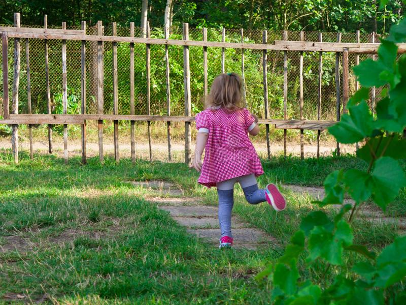 Weinig babymeisje die in de yard dichtbij het huis spelen royalty-vrije stock afbeelding