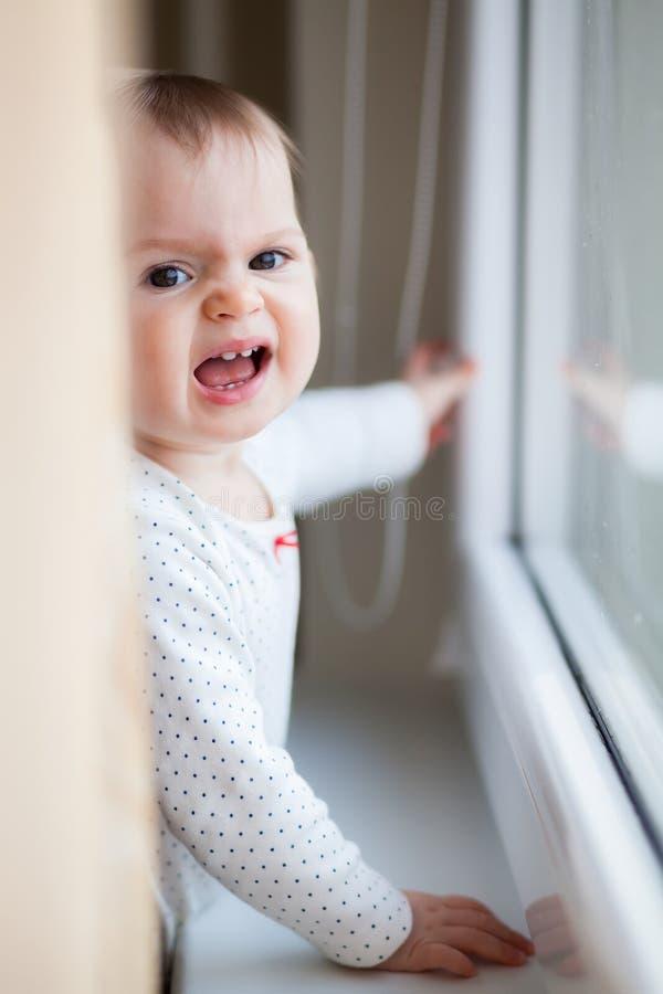 Weinig babymeisje die dichtbij het venster gillen royalty-vrije stock foto's