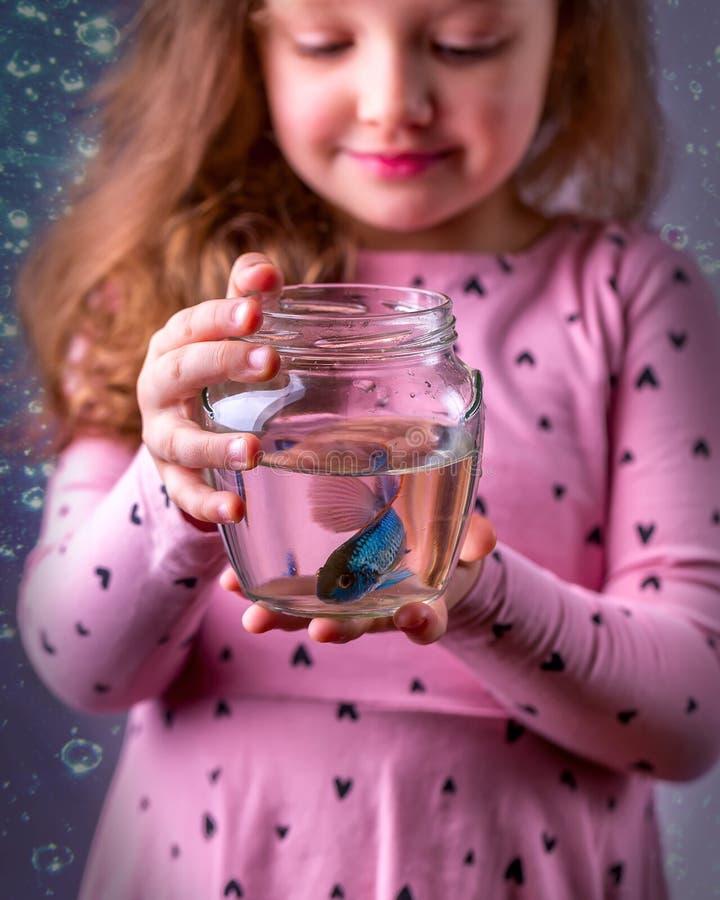 Weinig babymeisje die een fishbowl met een blauwe vis houden Zorgconce royalty-vrije stock foto's