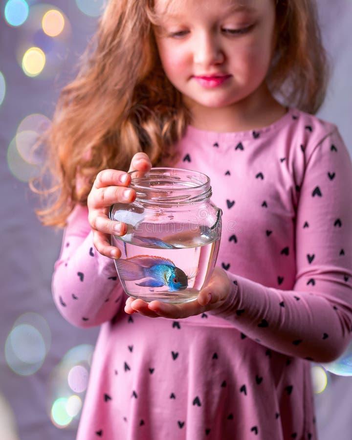 Weinig babymeisje die een fishbowl met een blauwe vis houden Zorgconce stock afbeelding