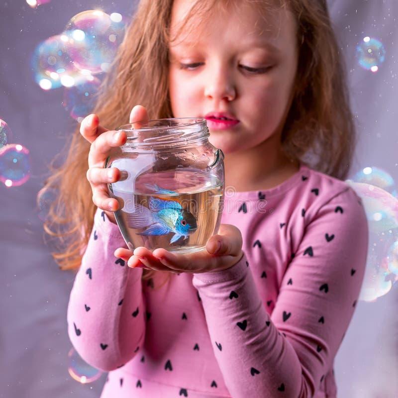 Weinig babymeisje die een fishbowl met een blauwe vis houden Zorgconce royalty-vrije stock afbeelding