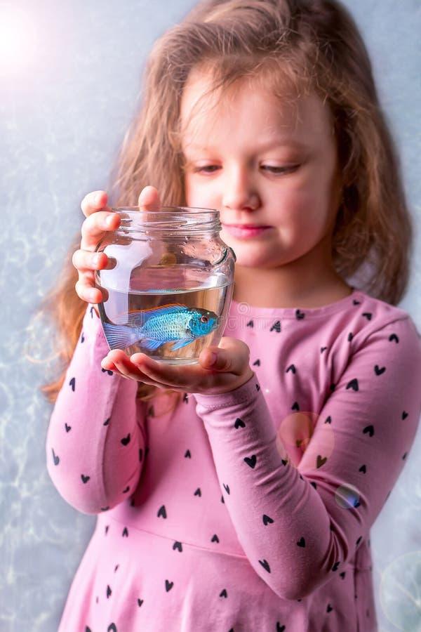 Weinig babymeisje die een fishbowl met een blauwe vis houden Zorgconce stock foto