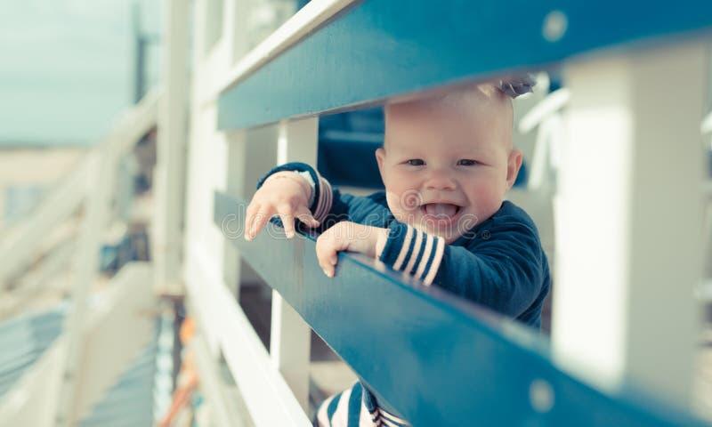 Weinig babymeisje die en pret op een beachhouse hebben lachen stock foto