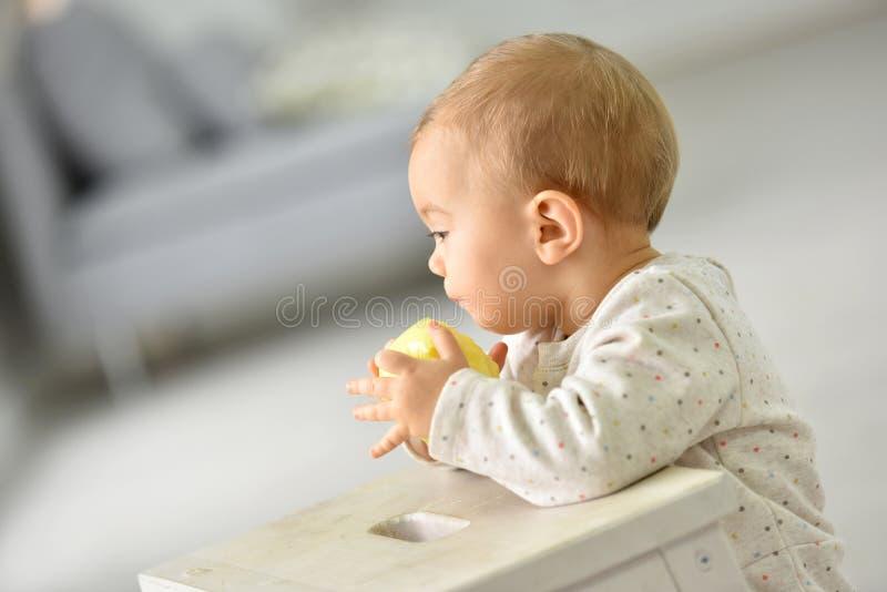 Weinig babymeisje die gele appel eten royalty-vrije stock afbeelding