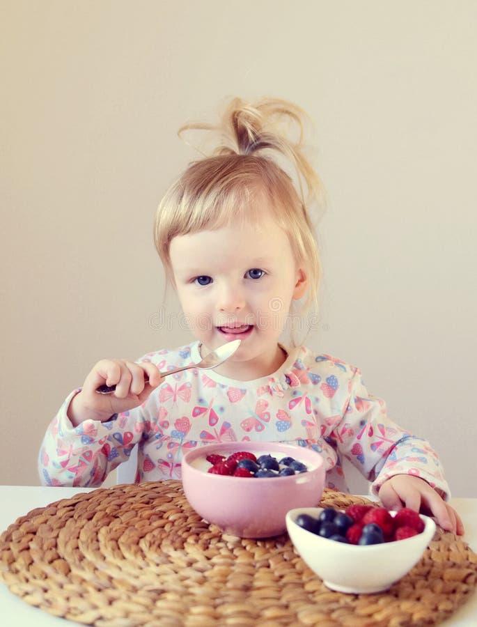 Weinig babymeisje die gezond ontbijt thuis, bessen en yoghurt eten royalty-vrije stock foto's