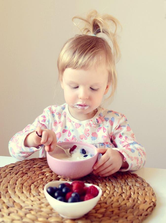 Weinig babymeisje die gezond ontbijt thuis, bessen en yoghurt eten stock fotografie