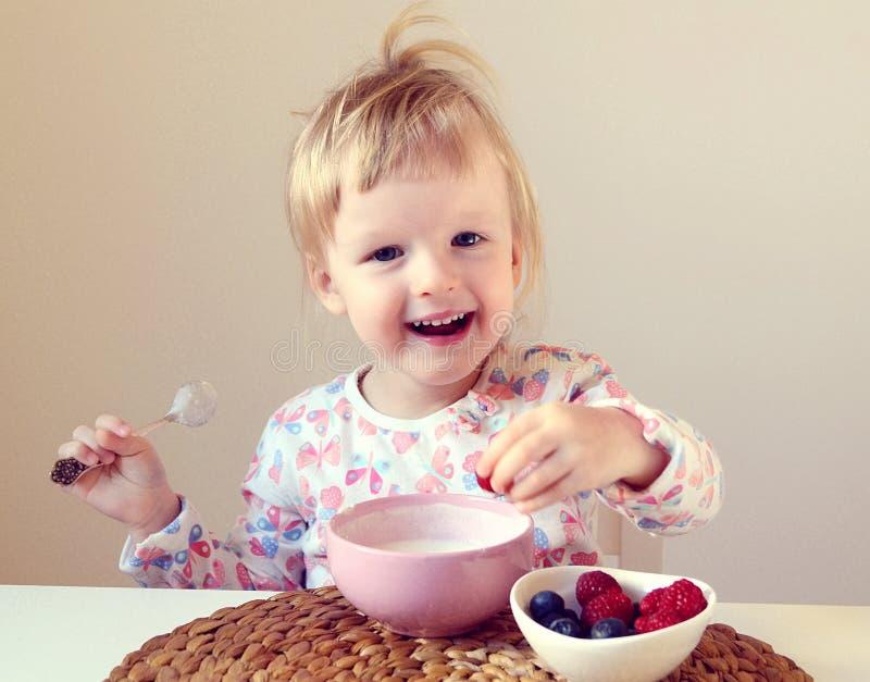 Weinig babymeisje die gezond ontbijt thuis, bessen en yoghurt eten stock foto