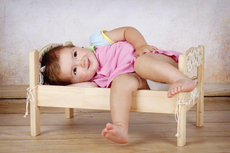 Weinig babymeisje die in het kleine bed liggen royalty-vrije stock foto's