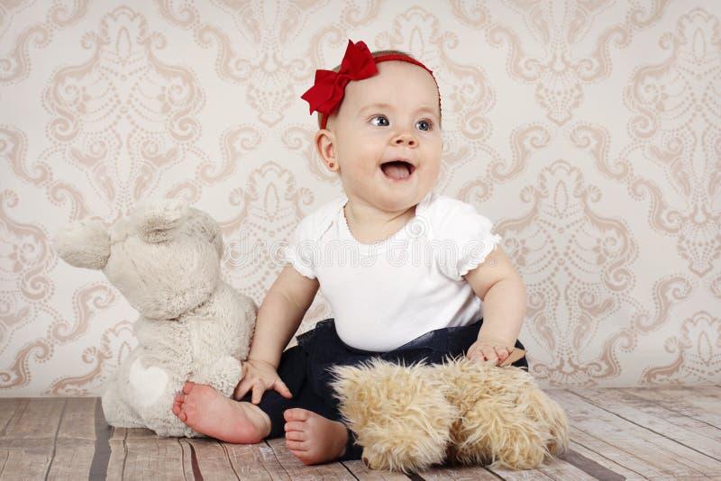 Weinig babymeisje die met pluchespeelgoed spelen stock foto's