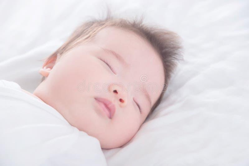 Weinig babymeisje die witte doekslaap op wit bed dragen stock foto