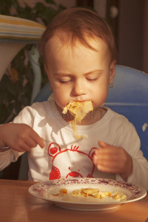 Weinig babymeisje eet pannekoeken met kaasdiner, kinderen ` s F stock foto