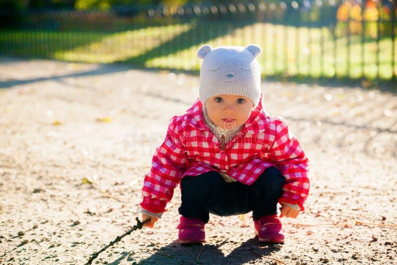 Weinig babymeisje met een stok stock afbeelding