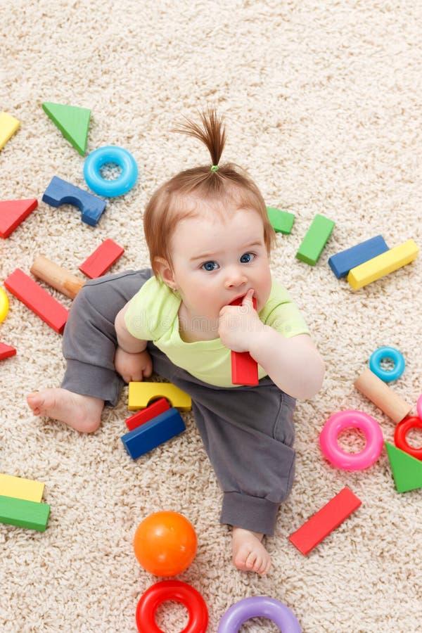 Weinig babymeisje in midden van speelgoed royalty-vrije stock foto
